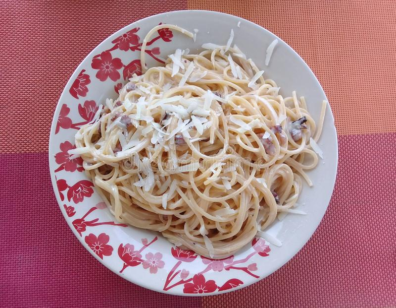El carbonara de los espaguetis en un plato con las flores diseña fotografía de archivo libre de regalías