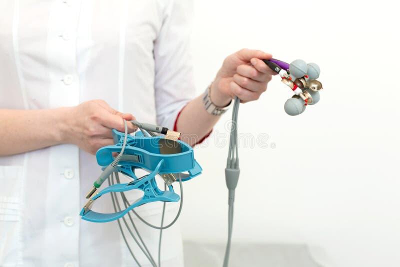 El cardiólogo sostiene los sensores del electrocardiógrafo en sus manos antes de conectarlas con el sistema fotografía de archivo libre de regalías