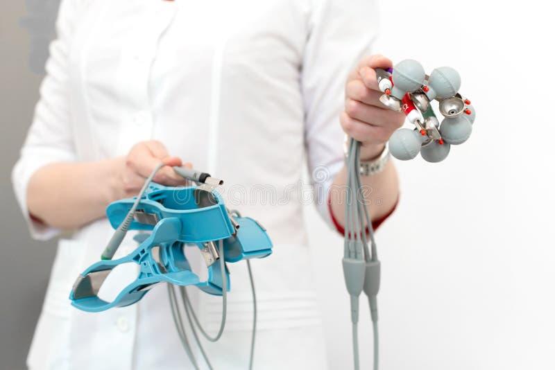El cardiólogo sostiene los sensores del electrocardiógrafo en sus manos antes de conectarlas con el sistema imágenes de archivo libres de regalías