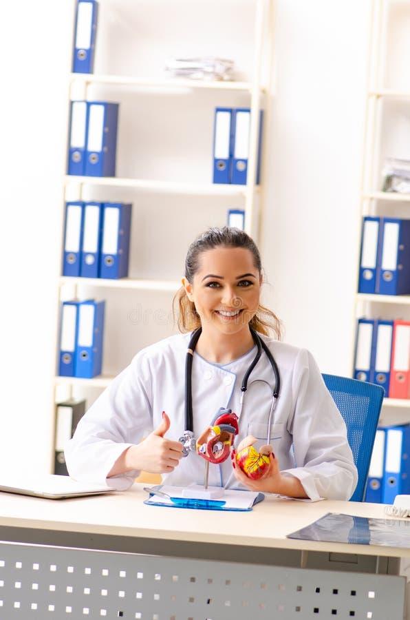 El cardi?logo de sexo femenino joven del doctor que se sienta en el hospital imagen de archivo libre de regalías