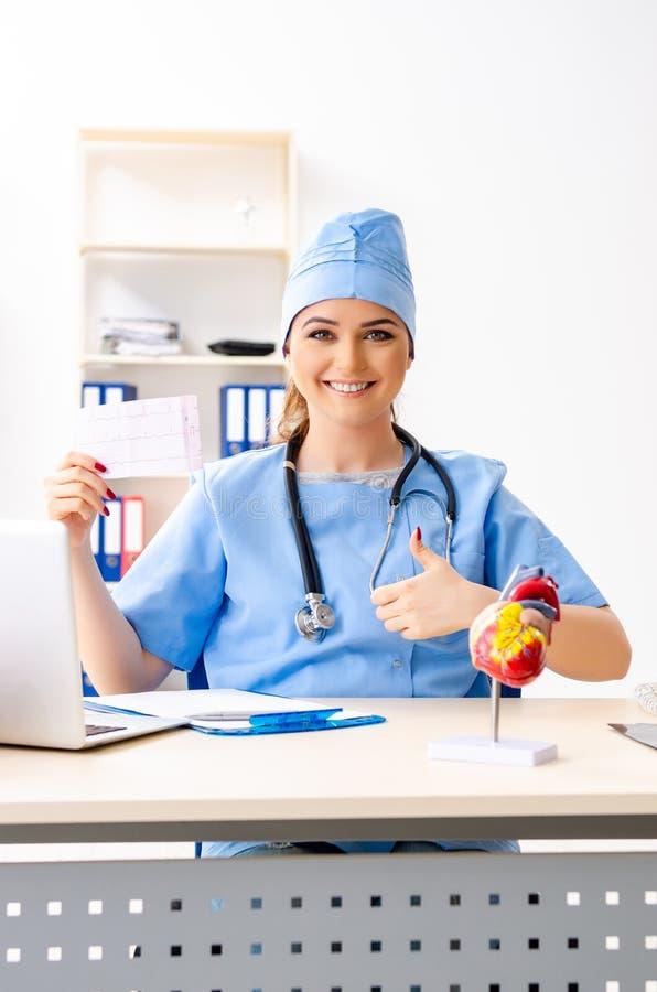 El cardi?logo de sexo femenino joven del doctor que se sienta en el hospital fotos de archivo libres de regalías