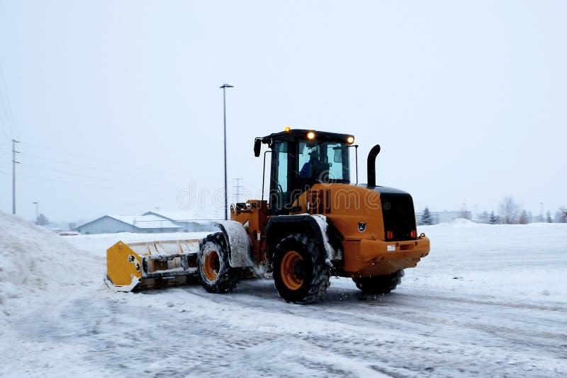 El cargador de la parte frontal trabaja como máquina de la retirada de la nieve que despeja un estacionamiento imágenes de archivo libres de regalías