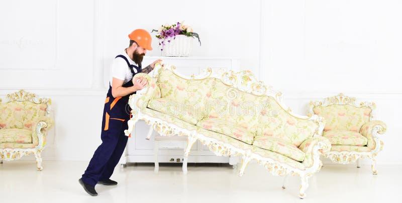 El cargador mueve el sofá, sofá El mensajero entrega los muebles en caso de se mueve hacia fuera, relocalización Concepto del ser foto de archivo libre de regalías