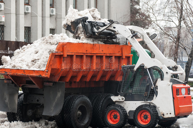 El cargador vierte la nieve en el camión fotos de archivo libres de regalías