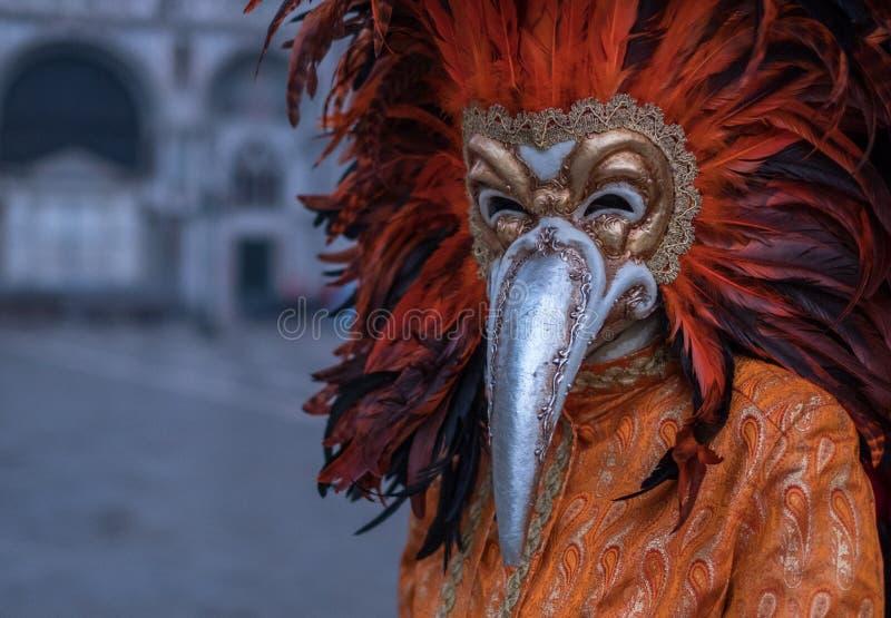 El carnaval-asistente vestido con rojo emplumó la máscara que se colocaba en cuadrado del ` s de St Mark durante los di Venezia d imagen de archivo