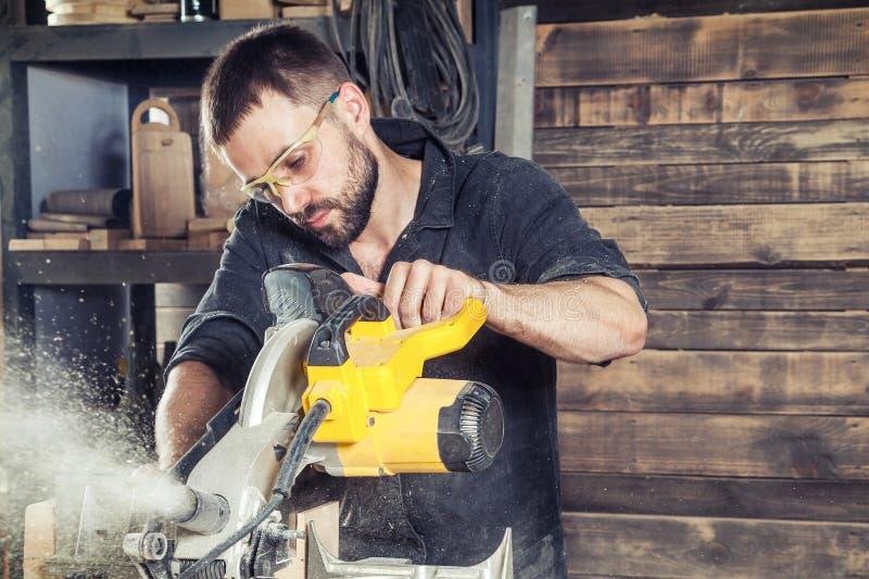 El carpintero asierra una sierra circular moderna fotos de archivo libres de regalías