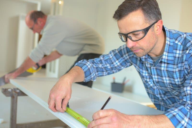 El carpintero canta cinta métrica foto de archivo