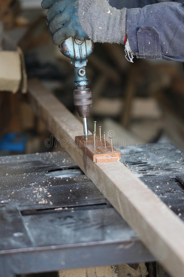 El carpintero compila de dos piezas de la madera con los tornillos imagen de archivo