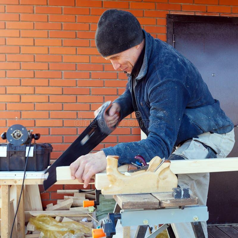 El carpintero con vio al aire libre imagenes de archivo
