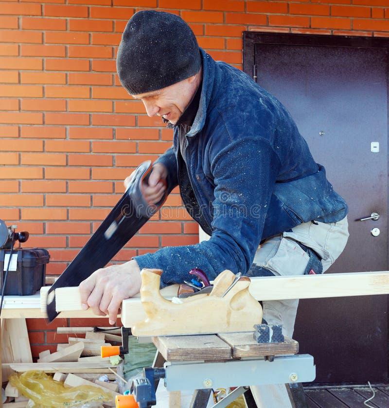 El carpintero con vio al aire libre imagen de archivo