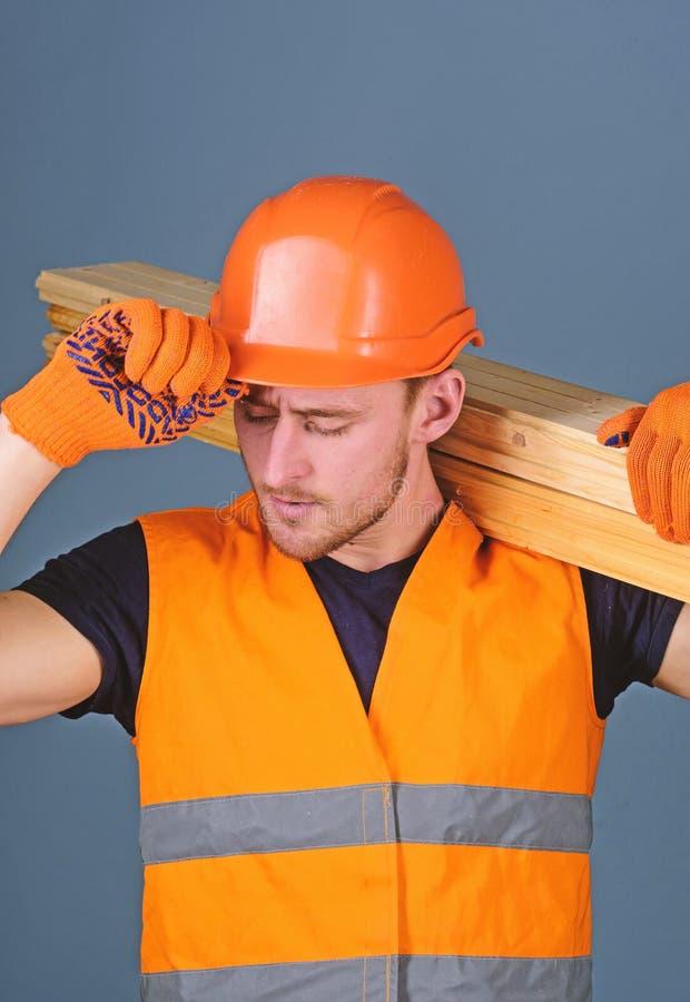 El carpintero, carpintero, constructor fuerte en cara ocupada lleva el haz de madera en hombro Concepto de la seguridad y de la p imagen de archivo libre de regalías