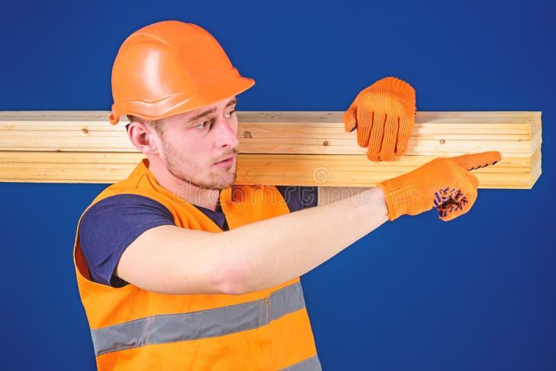 El carpintero, carpintero, constructor fuerte en cara ocupada lleva el haz de madera en hombro Hombre en el casco, casco y imagen de archivo