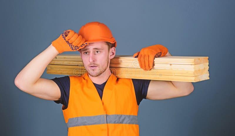 El carpintero, carpintero, constructor fuerte en cara seria lleva el haz de madera en hombro Hombre en el casco, casco y foto de archivo libre de regalías