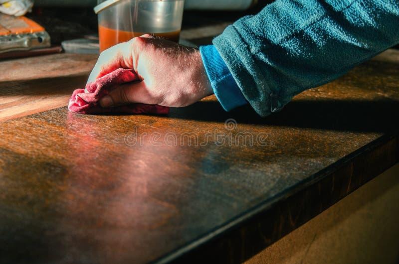 El carpintero cubre las piezas de madera de los muebles con la cera de madera foto de archivo libre de regalías