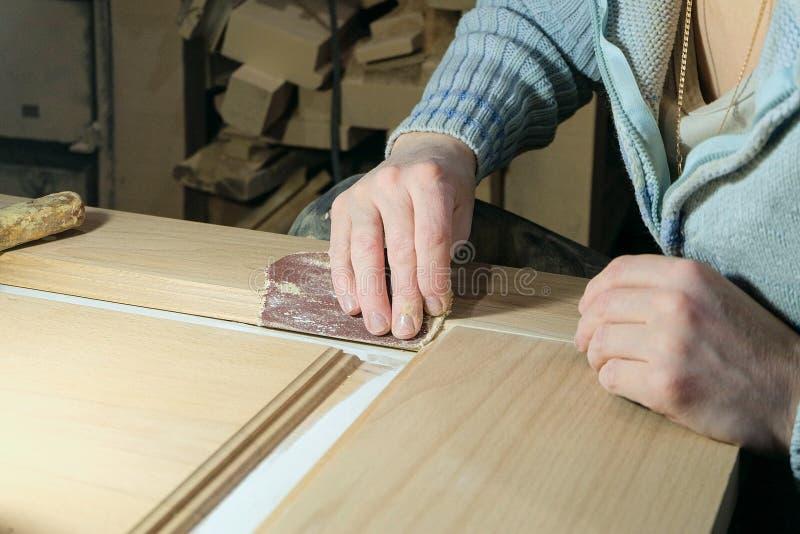 El carpintero de la mujer limpia la superficie del papel de lija de la hoja de la puerta en la tienda de la carpintería imagen de archivo