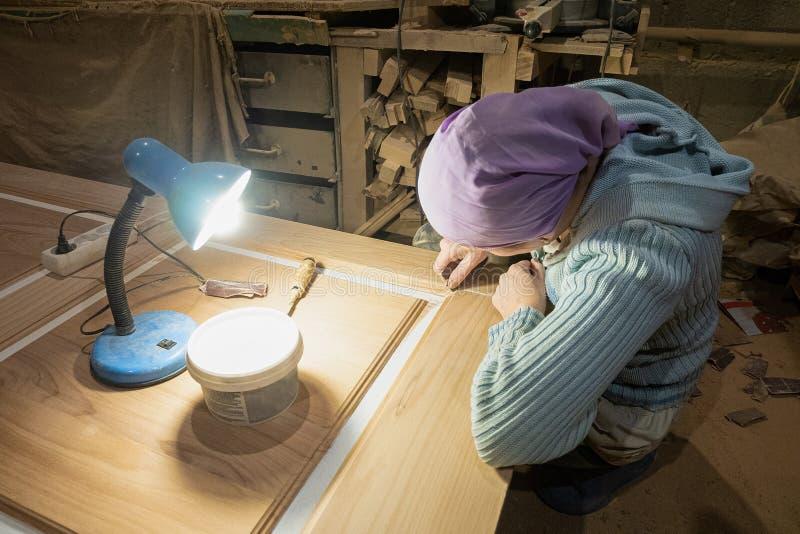 El carpintero de la mujer limpia y la superficie de las polainas de la masilla de la hoja de la puerta en la profesión de la tien fotografía de archivo libre de regalías
