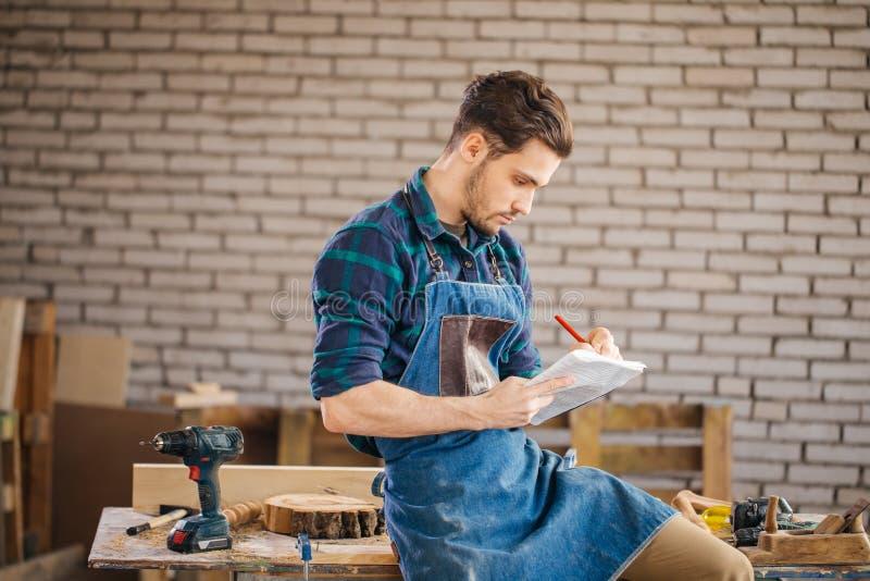 El carpintero del hombre en su estudio casero dibuja bosquejos en lápiz en cuaderno fotos de archivo