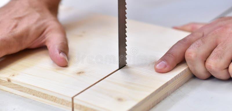 El carpintero en el taller asierra a un tablero de madera con una sierra fotos de archivo