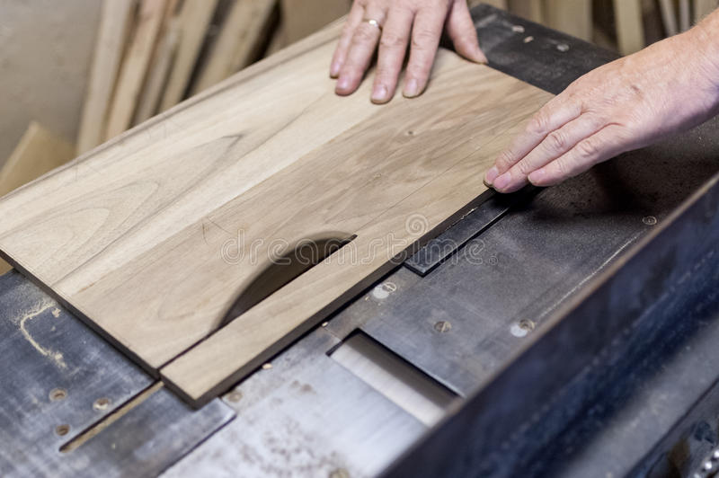 El carpintero está cortando a un tablero con la sierra eléctrica imagen de archivo libre de regalías