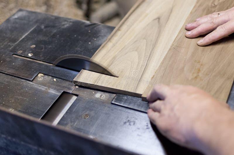 El carpintero está cortando a un tablero con la sierra eléctrica imágenes de archivo libres de regalías
