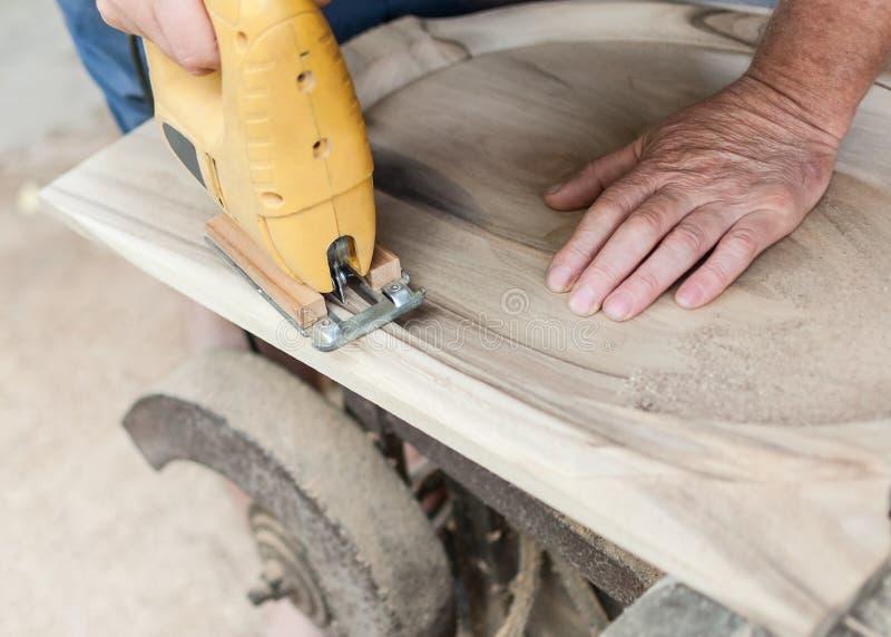 El carpintero está cortando a un tablero con segueta fotos de archivo libres de regalías