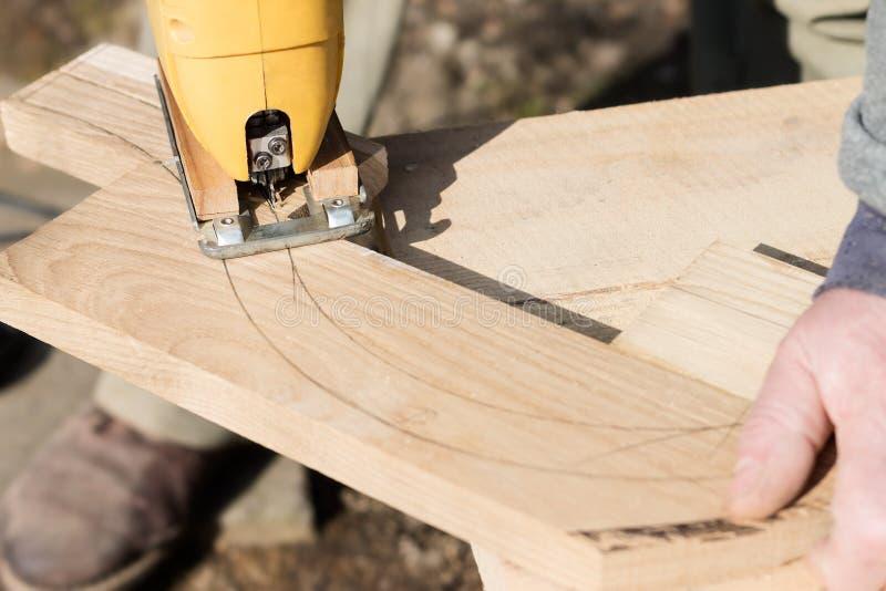 El carpintero está cortando a un tablero con segueta imagenes de archivo