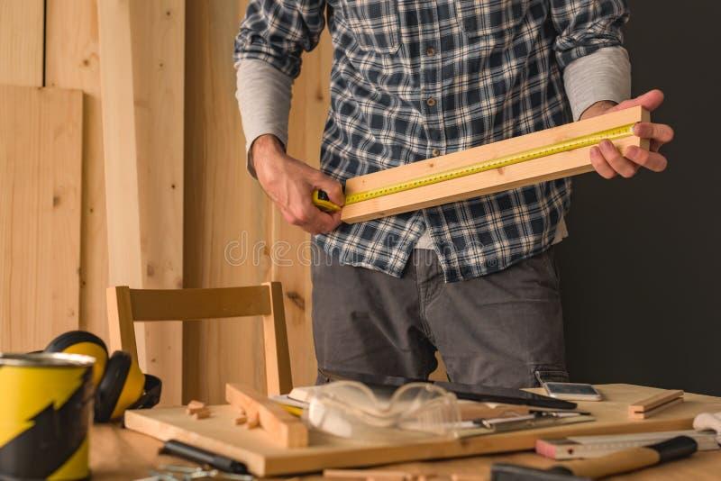 El carpintero está midiendo el tablón de madera de pino fotografía de archivo libre de regalías