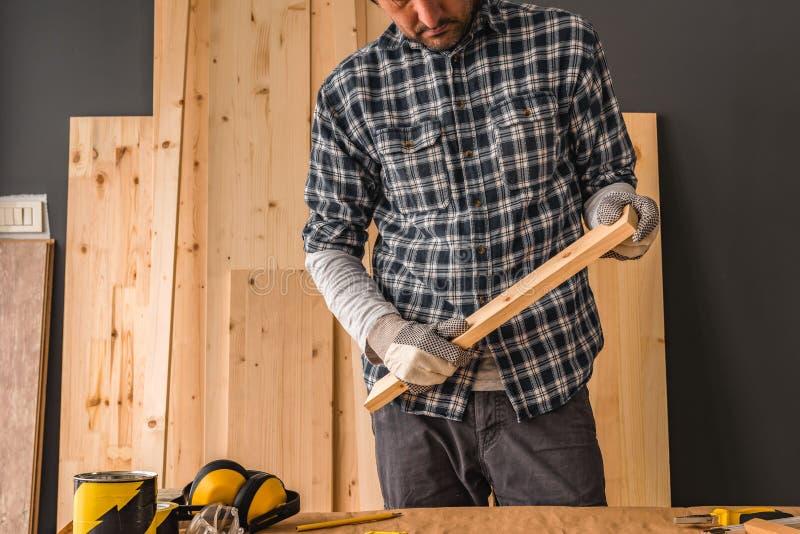 El carpintero está sosteniendo el pequeño tablón del pino en taller imagen de archivo