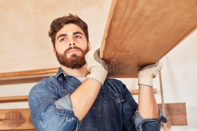 El carpintero joven en el entrenamiento está llevando haces foto de archivo libre de regalías