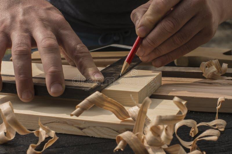 el carpintero marca con un lápiz rojo un tablón fotos de archivo libres de regalías
