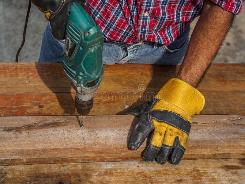 El carpintero perfora un agujero con un taladro eléctrico profesión, Ca fotos de archivo