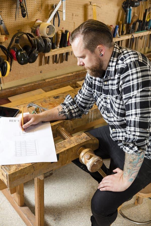 El carpintero planea proyectos y toma notas sobre el dibujo en taller fotografía de archivo libre de regalías