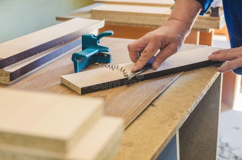 El carpintero procesa los espacios en blanco para la fabricaci?n de muebles imágenes de archivo libres de regalías