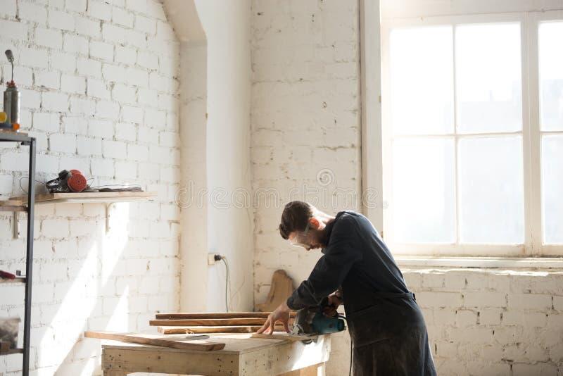 El carpintero profesional que usaba la mano del poder vio en el taller, cara VI foto de archivo libre de regalías