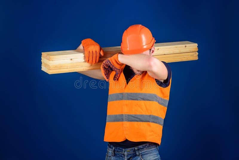 El carpintero, carpintero, trabajador, constructor en cara cansada lleva el haz de madera en hombro Concepto cansado del trabajad fotografía de archivo