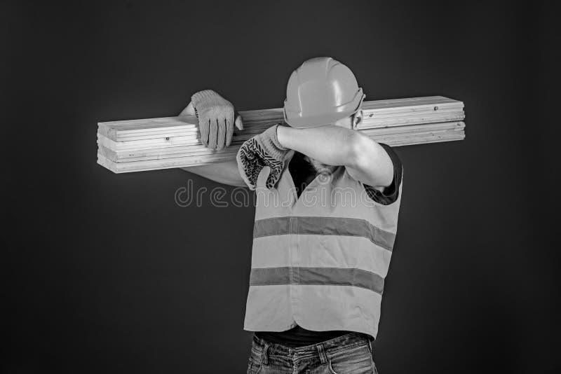 El carpintero, carpintero, trabajador, constructor en cara cansada lleva el haz de madera en hombro Concepto cansado del trabajad foto de archivo libre de regalías