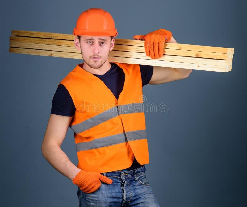 El carpintero, carpintero, trabajador, constructor en cara confiada lleva haces de madera en hombro Concepto resistente del traba fotografía de archivo