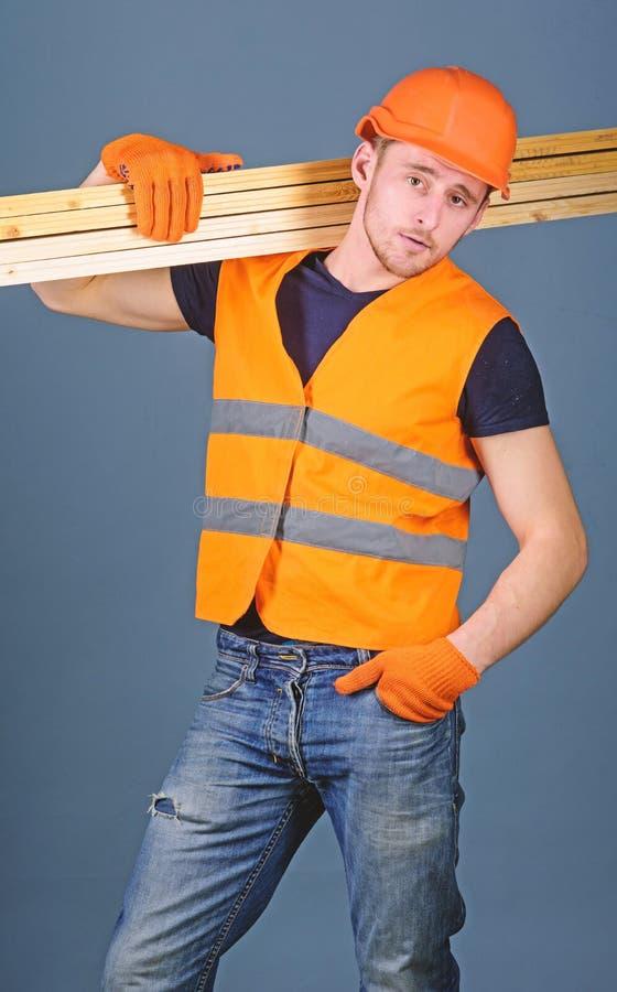 El carpintero, carpintero, trabajador, constructor en cara confiada lleva haces de madera en hombro Hombre en el casco, casco y foto de archivo