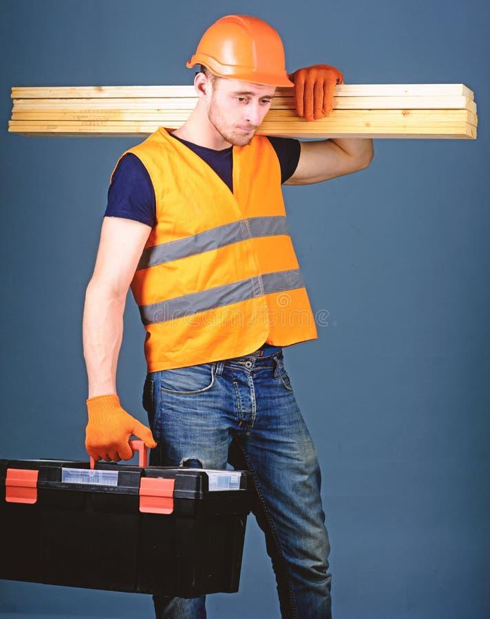 El carpintero, carpintero, trabajador, constructor en cara tranquila lleva haces de madera en hombro Hombre en el casco, controle imagen de archivo
