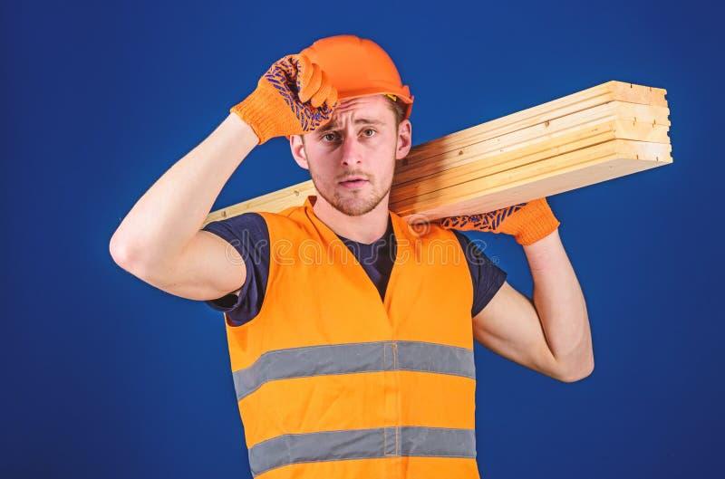 El carpintero, carpintero, trabajador, constructor lleva el haz de madera en hombro Concepto del carpintero Hombre en guantes pro imagenes de archivo