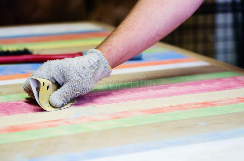 El carpintero trata la superficie de una tabla de madera con el paño de esmeril fotos de archivo