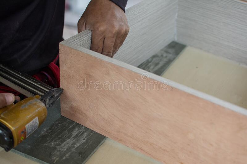 El carpintero usa una pistola de aire para hacer muebles nuevos imagen de archivo