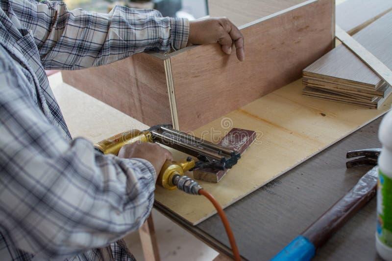 El carpintero usa una pistola de aire para hacer muebles nuevos foto de archivo libre de regalías