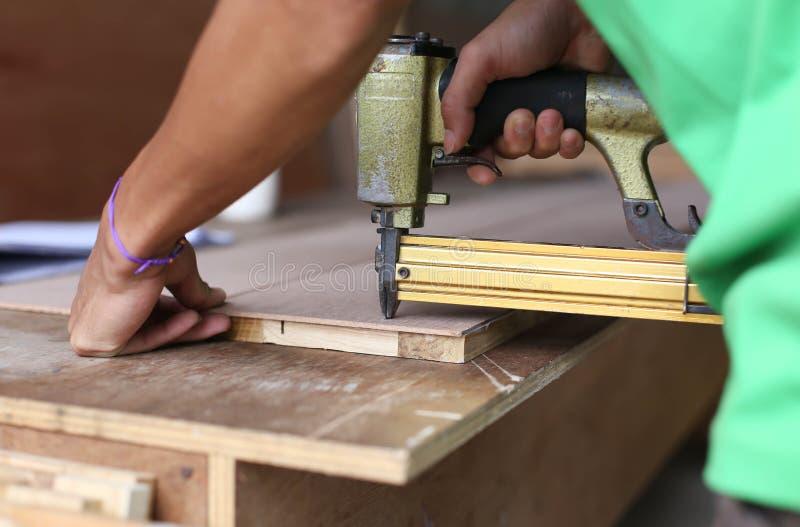 El carpintero utilizó un arma del clavo imagen de archivo libre de regalías
