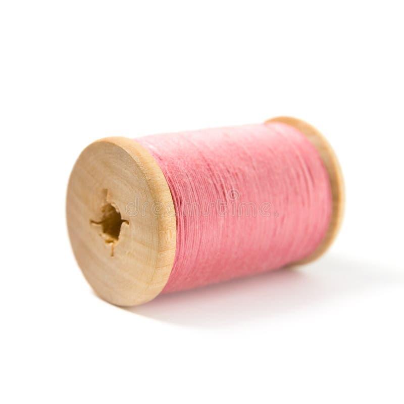 El carrete de madera con la cuerda de rosca rosada imagenes de archivo
