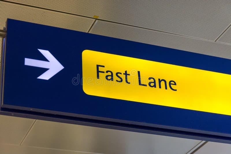 El carril rápido firma adentro azul y amarillo en el aeropuerto imagenes de archivo