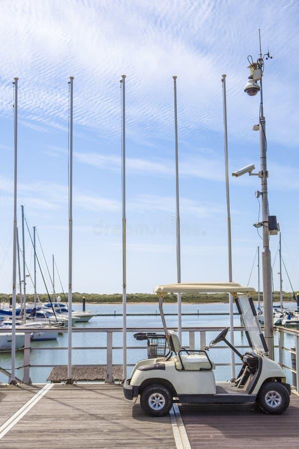 El carro de golf parqueó en el puerto deportivo del EL Rompido, España imagen de archivo
