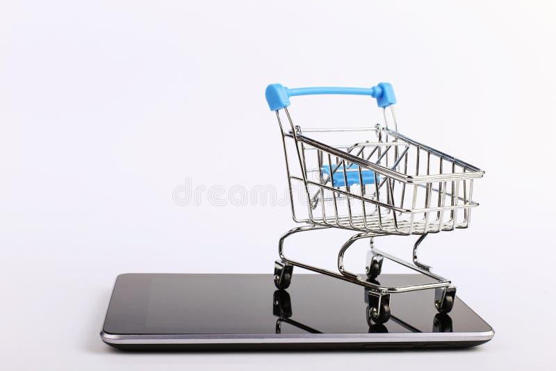 El carro de la compra se coloca en el smartphone Concepto en l?nea de las ventas fotografía de archivo libre de regalías