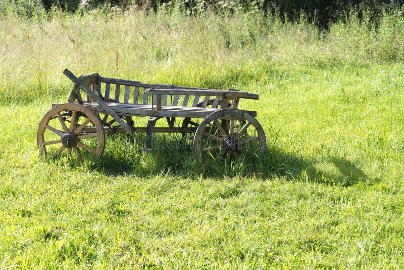 El carro de madera viejo se coloca en la hierba imagen de archivo