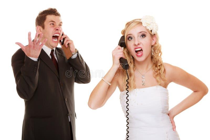 El casarse. Novia enojada y novio que hablan en el teléfono imagen de archivo